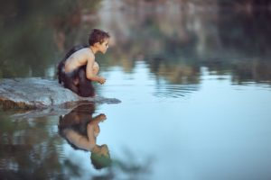 Boy looking at water hunting in stream dressed in cave wear - bargain hunting Llama Life