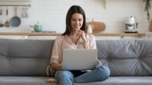 Women happy on couch with laptop looking please - Llama Life find that bargain